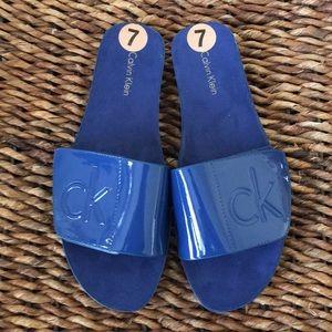 Calvin Klein blue patent leather adjustable slides